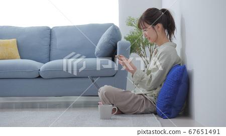 一個操作智能手機的女人 67651491