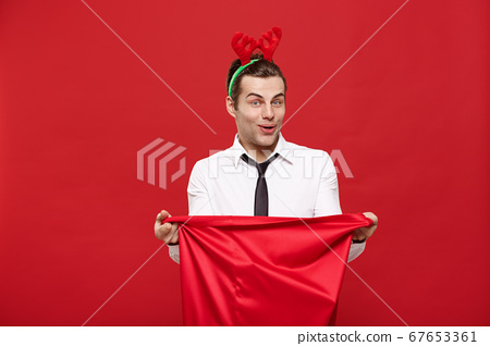 Christmas Concept - Handsome Business man celebrate merry christmas and happy new year wear reindeer hairband holding Santa red big bag. 67653361