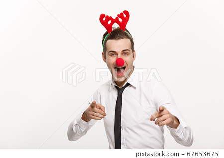 Christmas Concept - Handsome Business man wearing reindeer hairband making funny facial expression. 67653675