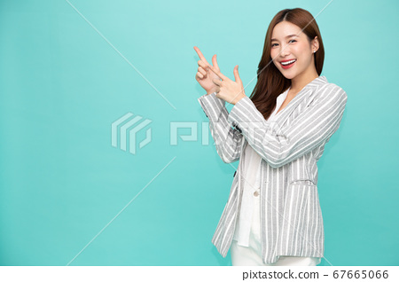 Young Asian woman smiling and pointing finger to empty copy space isolated on green background 67665066