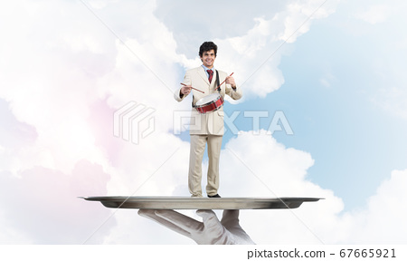 Young businessman on metal tray playing drums against blue sky background 67665921