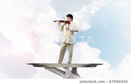 Businessman on metal tray playing violin against blue sky background 67666040