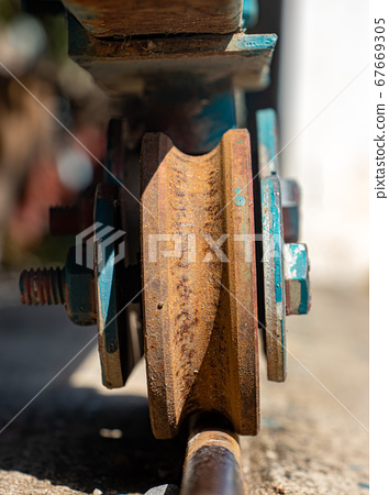 A rusty wheel from sliding gate on a rail, close 67669305