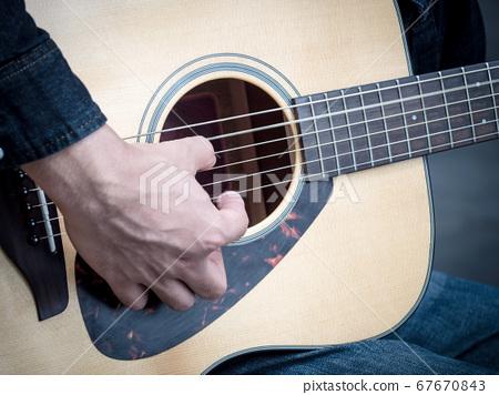 Male hand playing beautiful folk guitar.  67670843