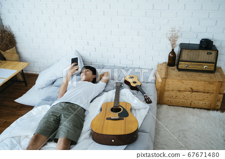 Lie down with guitar and ukulele. 67671480