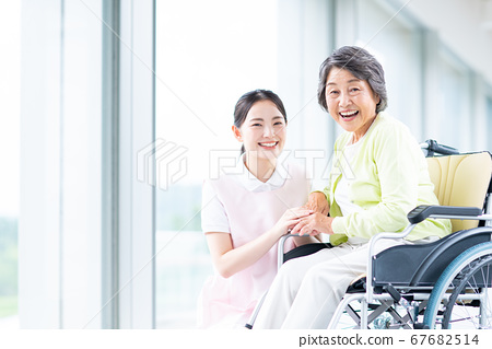 Senior woman in wheelchair and nursing staff 67682514