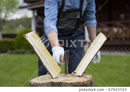 Close up lumberjack chopping wood with ax, sawdust fly to sides, harvesting wood 67683583