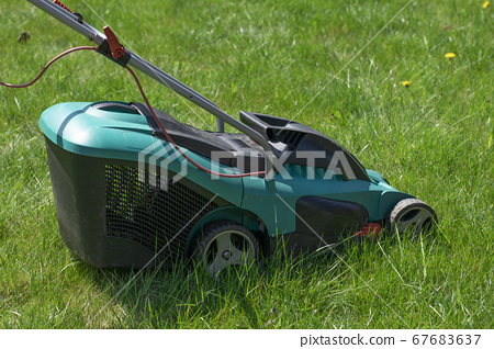 lawn mower standing on green lawn with yellow dandelions 67683637