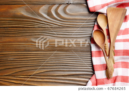 Red checkered napkin and wooden utencils on brown 67684265