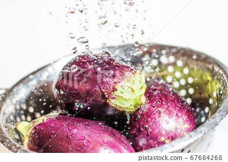 Eggplants being washed in colander under tap fresh 67684268