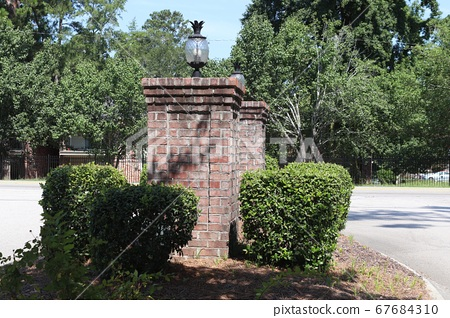 Nice flower bed with well-kept shrubs next to two red brick towers 67684310