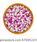 Diced red onions in wooden bowl. Cut cubes of onion cultivar Allium cepa, with purplish red skin and white flesh tinged with red. Closeup, from above, on white background, isolated, macro food photo. 67685224