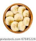 Fresh banana slices in wooden bowl. Ripe and peeled banana cut into round pieces. Edible and ready to eat dessert fruit with slightly yellow color. Closeup from above, over white, isolated food photo. 67685226