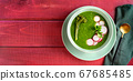 Top view of a green broccolini spinach cream soup on red rustic background 67685485
