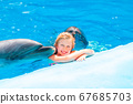 Happy little girl swimming with dolphins in 67685703