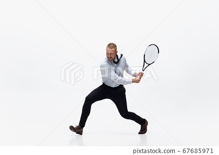 Time for movement. Man in office clothes plays tennis isolated on white studio background. 67685971