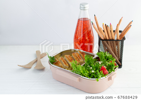 Lunch box with healthy meal and fruit juice for school children on white background next to stationery 67688429