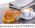A croissant and a cup of cappuccino, a newspaper in the background 67688442