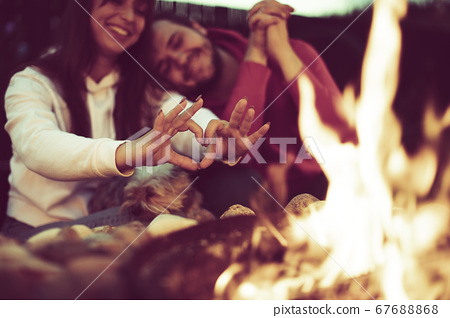 Young family with their dog rests near camping and woman shows heart with hands. 67688868