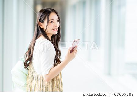 一名在校園裡操作智能手機的大學生 67695388