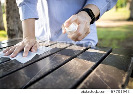 Hand of woman is spraying alcohol,wiping the dirt,disinfectant spray on table,during the pandemic of Covid-19,Coronavirus,cleaning,disinfecting wipe the public wooden table at park,hygienic for safety 67701948
