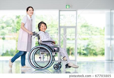 Senior woman in wheelchair and nursing staff 67703805