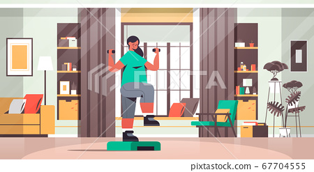 woman doing exercises with dumbbells on step platform at home girl having workout cardio fitness training 67704555