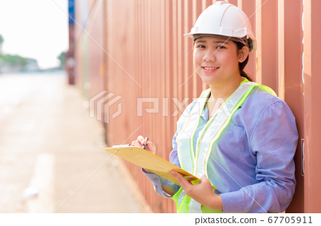 Asian young teen happy worker checking stock in shipping port work manage import export 67705911