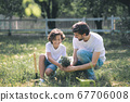 Dark-haired boy and his dad holding the plant and talking 67706008