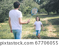 Dark-haired boy and his father playing badminton in the park 67706055