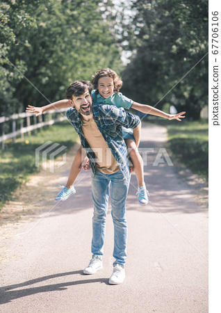 Dark-haired boy sitting on his fathers back with his hands to the sides 67706106