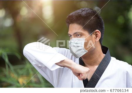 Man training Taekwondo at outdoor public park wearing face cover disposal face mask 67706134