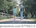 Dark-haired boy riding a skateboard, his father holding him 67706215