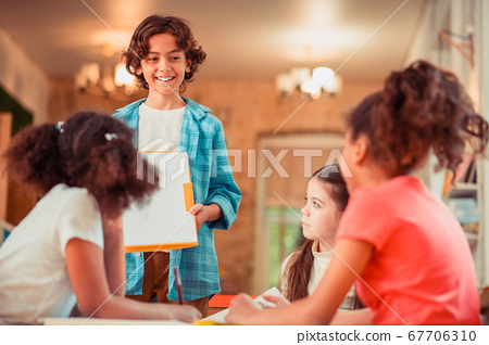 Young boy showing his project to his peers 67706310