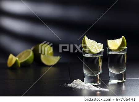 Tequila , lime and salt on black table. 67706441