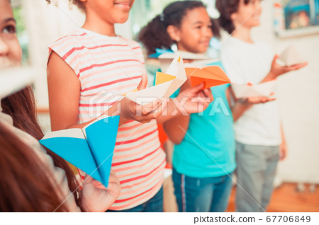 Group of schoolchildren holding their colorful paper crafts 67706849