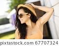 Pretty brunette girl in orange top smiling nicely 67707324