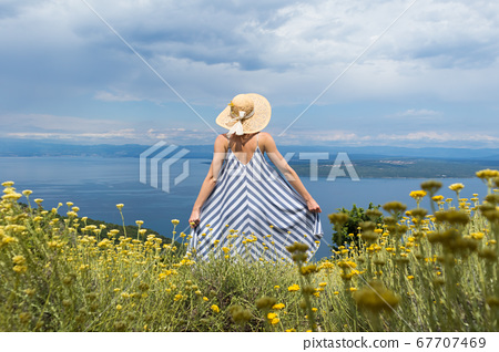Rear view of young woman wearing striped summer dress and straw hat standing in super bloom of wildflowers, relaxing while enjoing beautiful view of Adriatic sea nature, Croatia 67707469