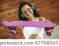Beautiful brunette girl showing a skateboard and smiling 67708503