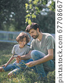 Dark-haired boy and his father looking at the plant through magnifying glass and looking interested 67708667