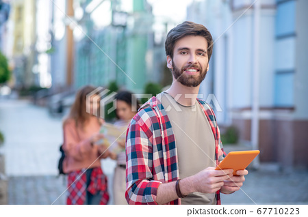Satisfied guy with a tablet traveling around the city 67710223