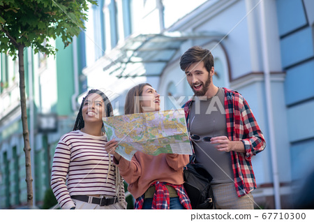 Astonished guy and two girls traveling around the city 67710300