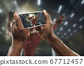 Close up hands holding smartphone viewing sport, online translation, streaming of championship 67712457