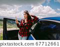 attractive woman travel by car and using smartphone in mountains 67712661
