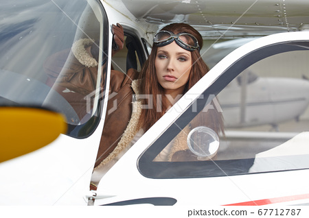 Young Woman Pilot With Headset Looking Through The 67712787