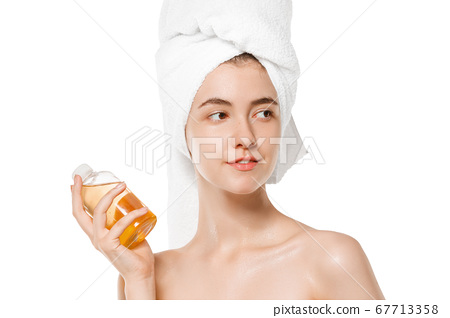 Beauty Day. Woman wearing towel doing her daily skincare routine isolated on white studio background 67713358