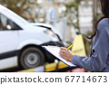 Insurance agent fills out paperwork after accident. 67714673