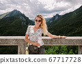 attractive woman traveller holding coffee mug with mountains view 67717728