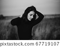 black and white portrait of a young girl posing Caucasian brunette girl in a sweater 67719107