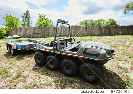 eight-wheeled all-terrain vehicle with a trailer on a meadow on a summer day 67720409